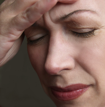 Woman holding head with headache